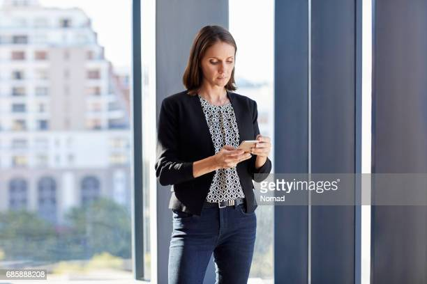 Mid adult businesswoman using mobile phone in creative office. Female executive is standing against window. She is wearing blazer.