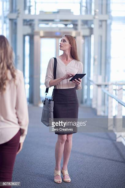 Mid adult businesswoman with digital tablet on conference centre walkway