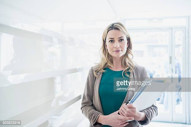 Mid adult businesswoman with paperwork, portrait