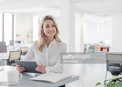 Mid adult businesswoman with tablet, looking away