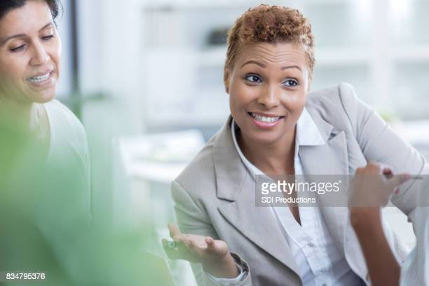 Mid adult businesswomen poses question during meeting