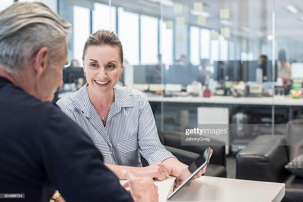 Metà adulto busineswoman utilizzando tablet con uomo maturo, sorridente : Foto stock