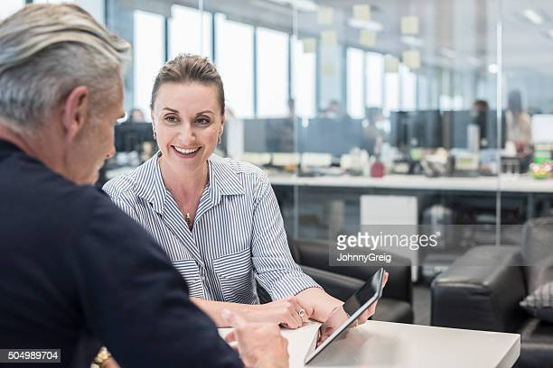 Mid adult busineswoman using tablet with mature man, smiling
