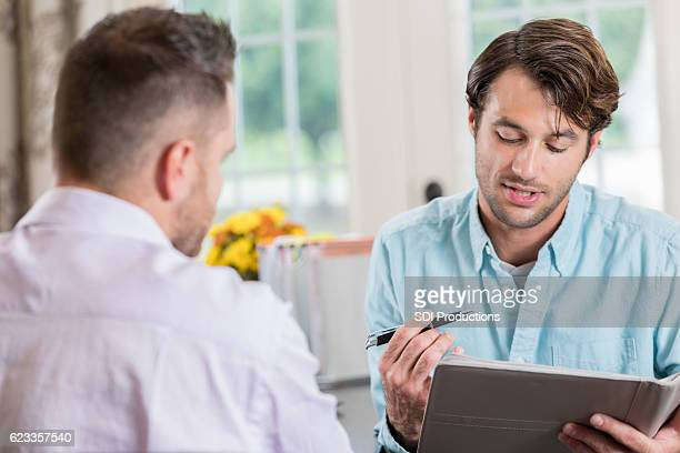 Mid adult Caucasian entrepreneur interviews man in home office