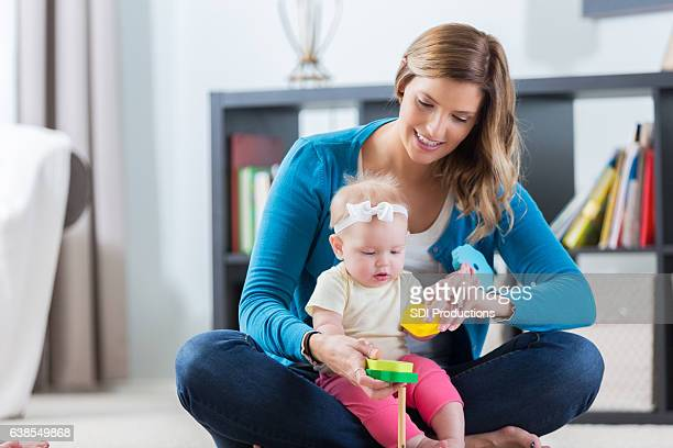 Mid adult Caucasian nanny plays with baby