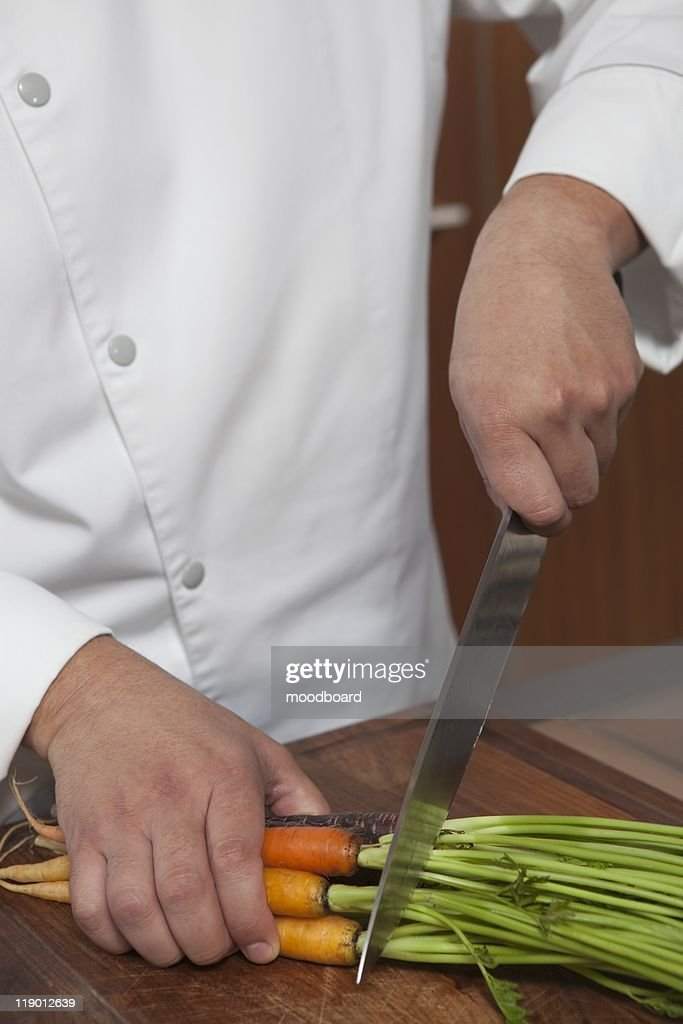 Mid- adult chef cutting carrots : Stock Photo