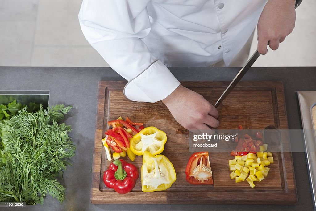 Mid- adult chef dices red and yellow bell peppers : Stock Photo