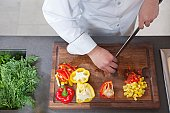 Mid- adult chef dices red and yellow bell peppers
