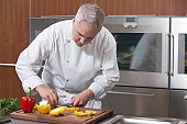 Mid- adult chef slices red and yellow bell peppers