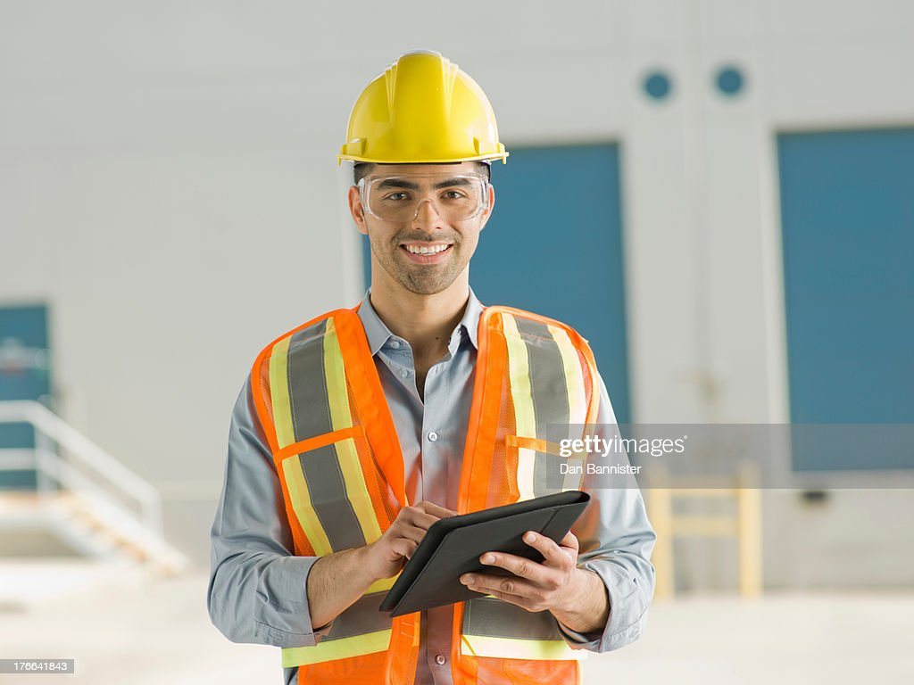 Mid adult construction worker using digital tablet, portrait
