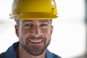 Mid adult construction worker wearing hard hat, smiling