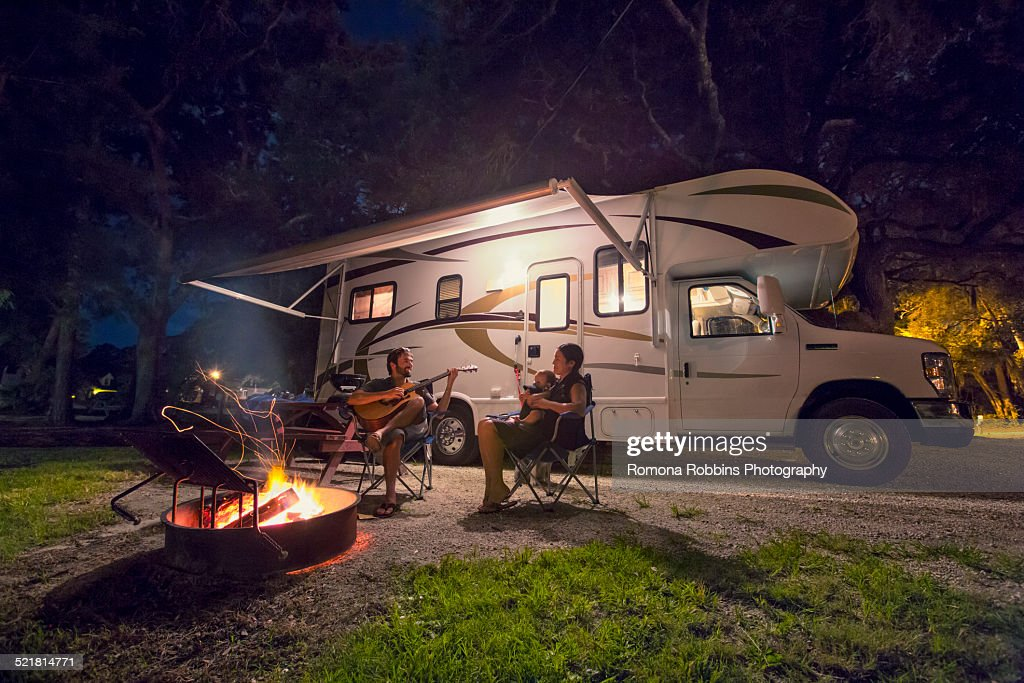 Mid adult couple and baby daughter sitting in front of campfire at night