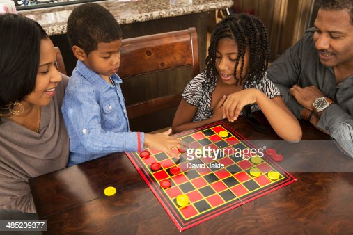 Mid adult couple and children playing draughts at dining table