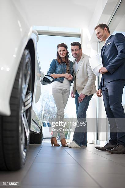 Mid adult couple and salesman looking at car in car dealership
