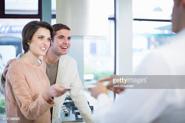 Mid adult couple and salesman looking at ceramic tile in kitchen showroom