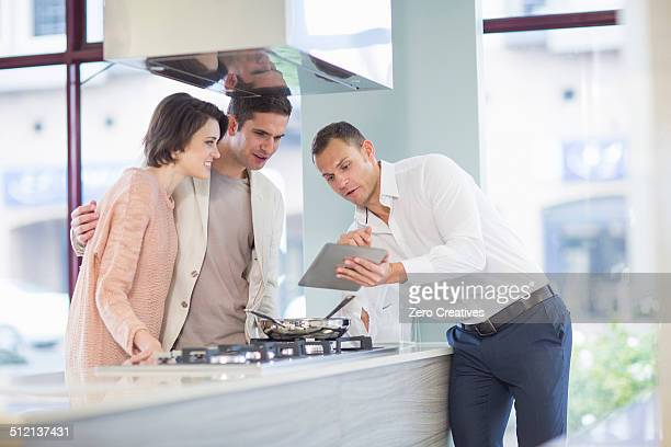 Mid adult couple and salesman looking at digital tablet in kitchen showroom