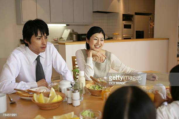 Mid adult couple and their daughters at the dining table