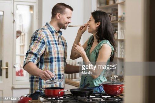 Mid adult couple cooking dinner, tasting