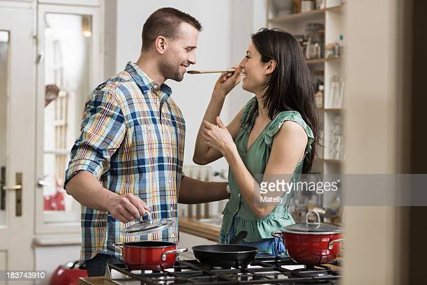 Mid adult couple cooking dinner, tasting