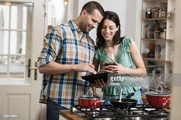 Mid adult couple cooking dinner, using digital tablet