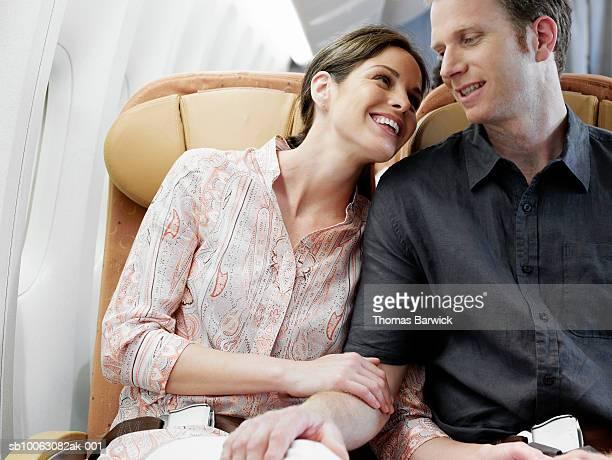 Mid adult couple cuddling on airplane