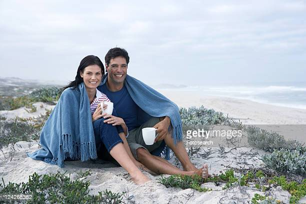 Mid adult couple drinking tea on beach, Cape Town, South Africa