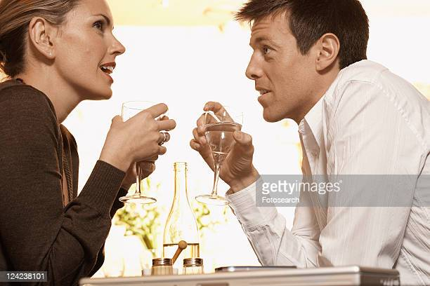Mid adult couple drinking water in restaurant (low angle view)
