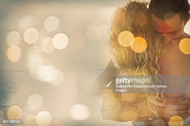 Mid adult couple embracing in sunlight