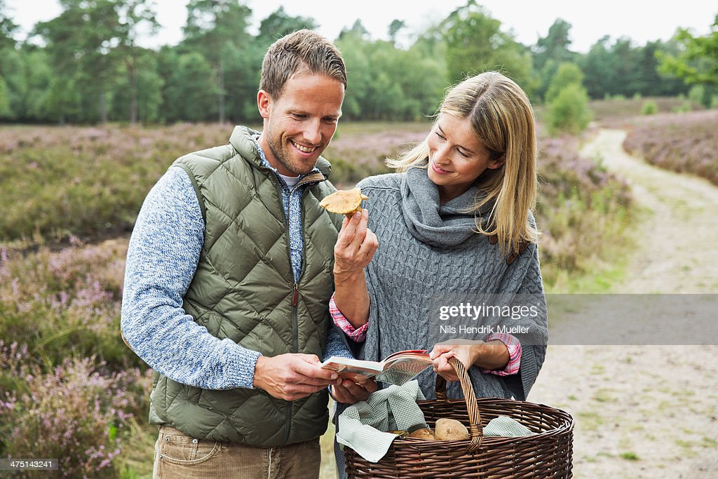 Mid adult couple foraging for mushrooms