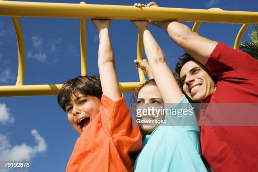 Mid adult couple hanging on monkey bars with their son and smiling : Foto de stock
