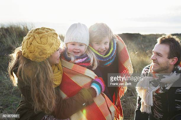 Mid adult couple in sand dunes with their son and daughter wrapped in blanket
