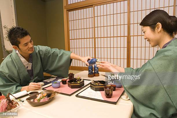 Mid Adult Couple in Yukata, Eating Dinner, Drinking Sake, Side View