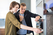 Mid adult couple inspecting oven in kitchen showroom