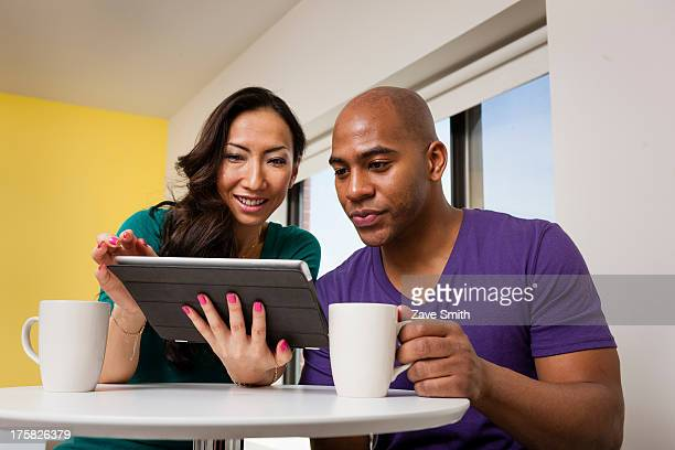 Mid adult couple looking at digital tablet and drinking coffee