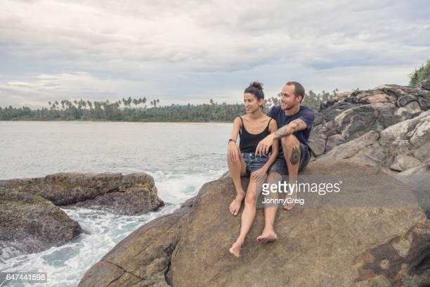 Mid adult couple looking at sea sitting on rocks, Sri Lanka