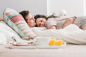 Mid adult couple lying in bed, breakfast on tray, hugging