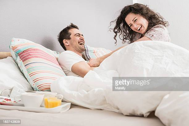 Mid adult couple lying in bed, breakfast on tray, pillow fight