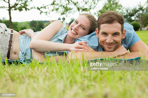 Mid adult couple lying on grass
