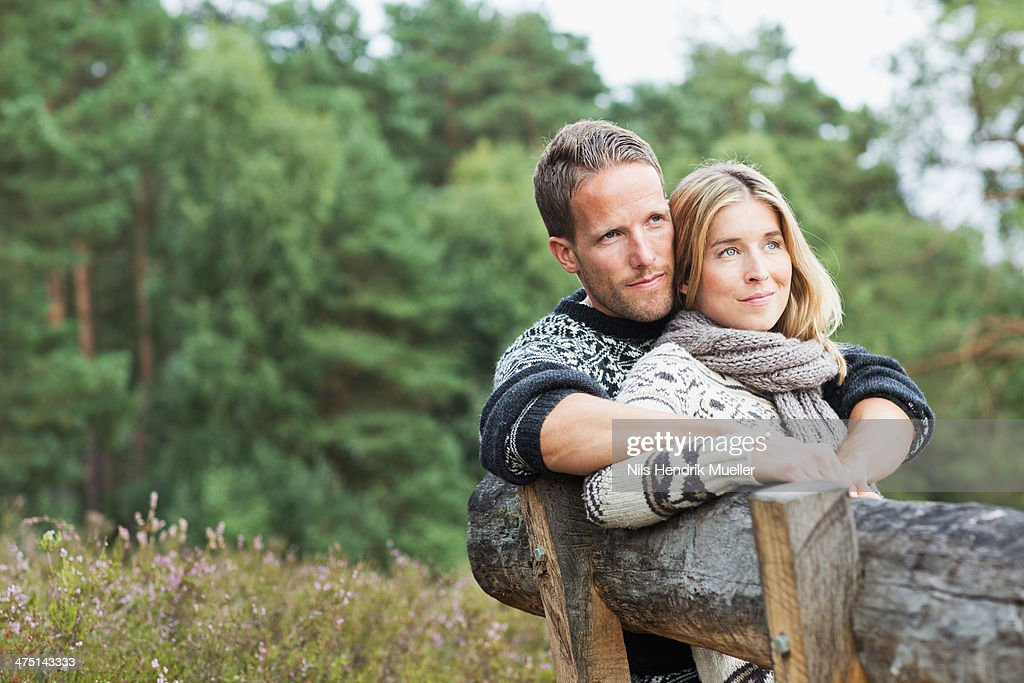 Mid adult couple on bench looking away
