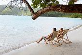 Mid adult couple on lounge chairs on beach (high angle view), St. John, US Virgin Islands, USA