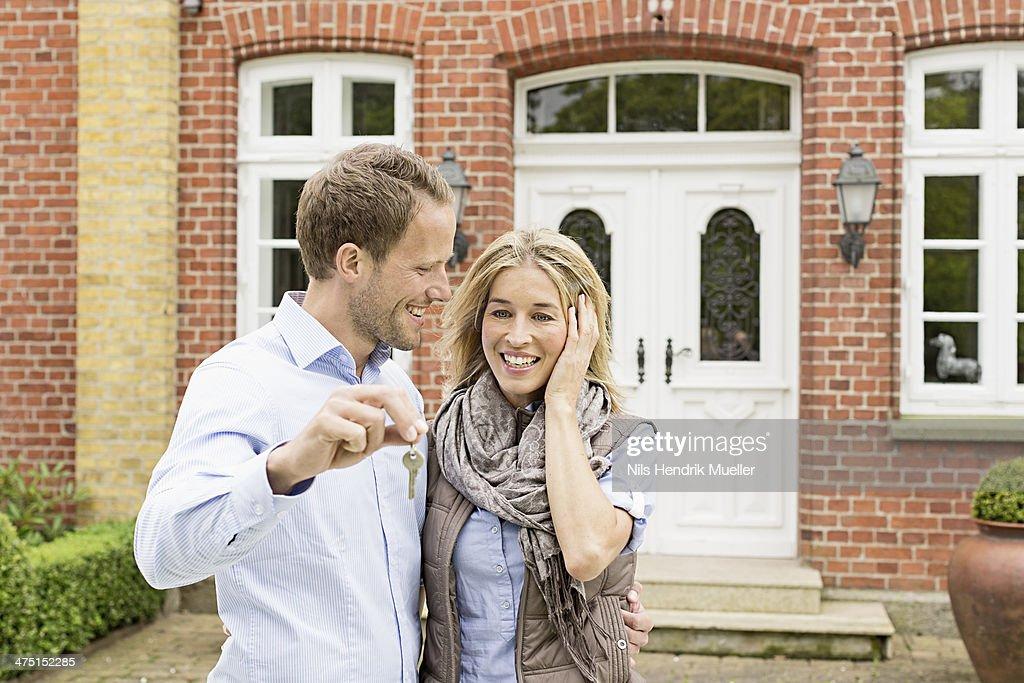 Mid adult couple outside house, man holding key
