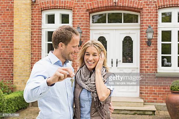 Mid adult couple outside house, man holding key