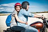 Mid adult couple riding motorcycle on arid plain, Cagliari, Sardinia, Italy