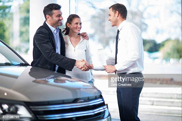 Mid adult couple shaking hands with salesman in car dealership