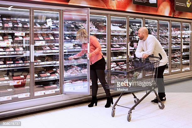 Mid adult couple shopping in supermarket