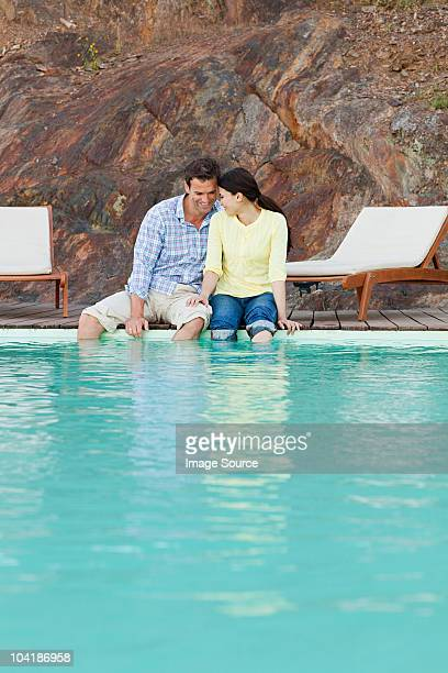 Mid adult couple sitting at poolside with legs dangling in water