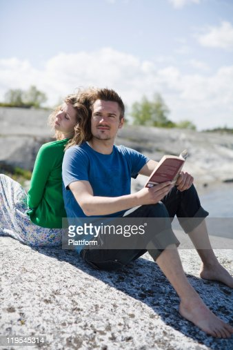 Mid adult couple sitting on beach and looking away, man holding book
