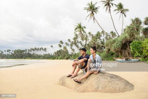 Mid adult couple sitting on rock on beach