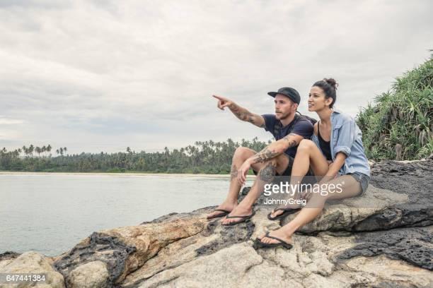 Mid adult couple sitting on rocks, man pointing
