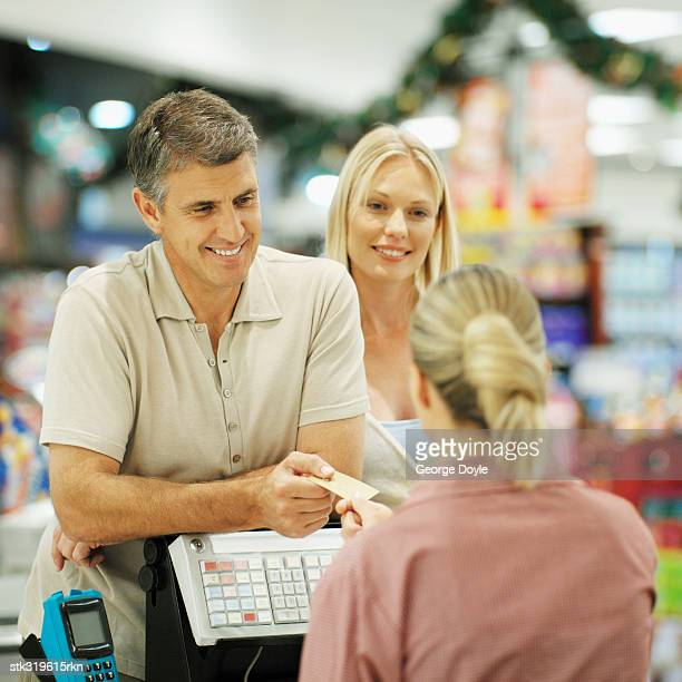 mid adult couple standing at a checkout counter in a supermarket